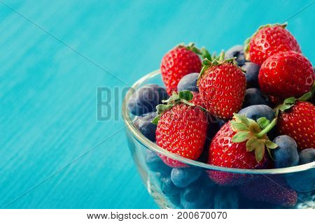 Berry Fresh in a copper cup on the blue Background. Blackberries, raspberry with mint. Food or Healthy diet concept. Super Food. Vegetarian. Copy space for Text. selective focus.