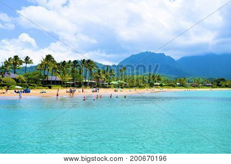 August 1, 2017 at Hanalei Bay in Kauai, HI:  People swimming and relaxing on the sandy beach beside lush plants and Palm Trees with mountains beyond taken at Hanalei Bay Beach where people can relax and swim in the warm ocean waters taken in Kauai, HI