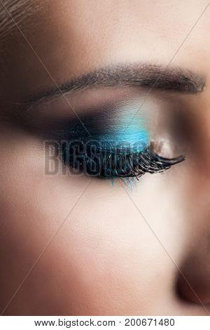 closeup of woman closeed eye with blue eye shadow studio shot