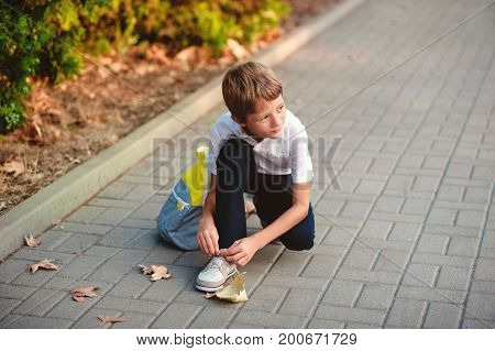 The pupil of the school goes to class. On the way he stopped to tie his shoelaces on his shoes.
