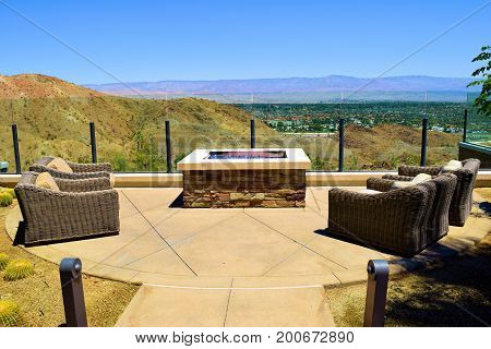 Contemporary outdoor patio furniture including comfortable chairs surrounding a fire pit overlooking the desert taken at a residential yard in Palm Springs, CA