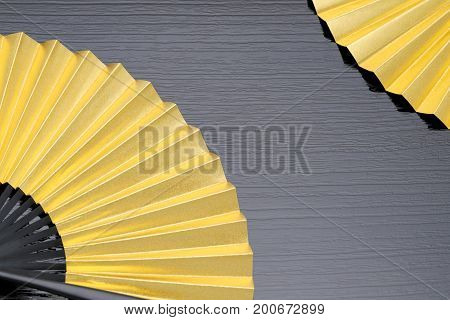 traditional golden folding fan on gray background
