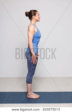 Woman doing Hatha Yoga asana Tadasana - Mountain pose with stretched hands on yoga mat in studio on grey bagckground