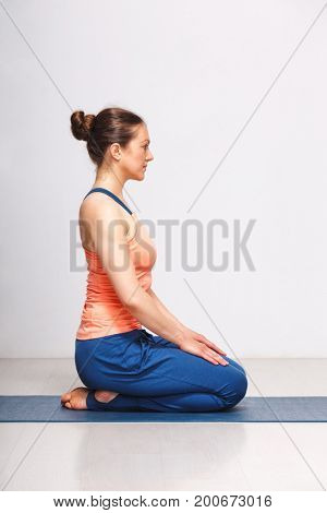 Woman in Hatha yoga asana Vajrasana - vajra pose or diamond pose on yoga mat on yoga mat in studio on grey bagckground