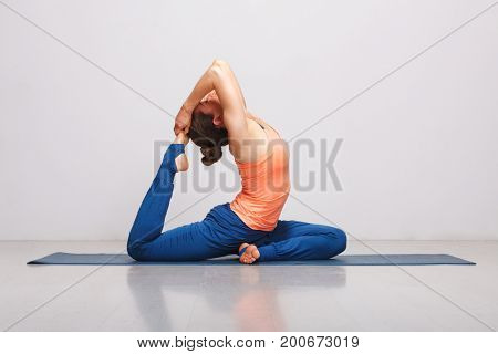 Woman doing Hatha yoga asana Eka pada rajakapotasana - one-legged king pigeon pose on yoga mat on yoga mat in studio on grey bagckground