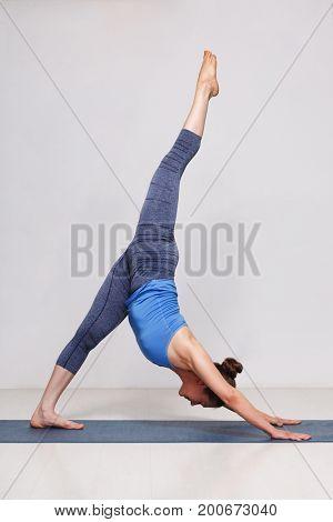 Woman doing Hatha yoga Eka pada adhomukha svanasana - one-legged downward facing dogon yoga mat in studio on grey bagckground