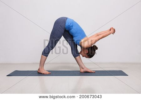 Woman doing Ashtanga Vinyasa yoga asana Parsvottanasana - intense side stretch pose on yoga mat in studio on grey bagckground