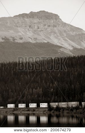 BANFF, CANADA - AUGUST 27: Cargo train lake and mountain on August 27, 2015 in Banff National Park, Canada. Established in 1885, it is the oldest park in Canada.