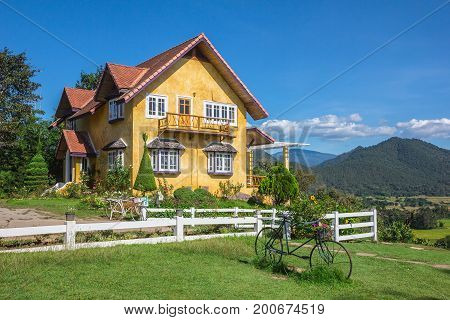 Charming yellow house and a beautiful sky background with garden and mountain in the back. Pai Mae Hong Son Thailand Conceptual image of Feng Shui.