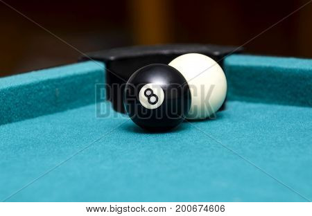 Eight ball and cue ball on pool table