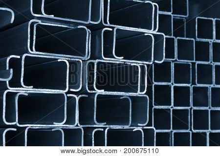The rectangle C shape of profile tube in the light blue scene.The closeup of the steel bar structure for construction in the shelf.
