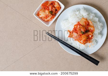 Rice with kimchi cabbage on top with chopsticks for eating,Korean food