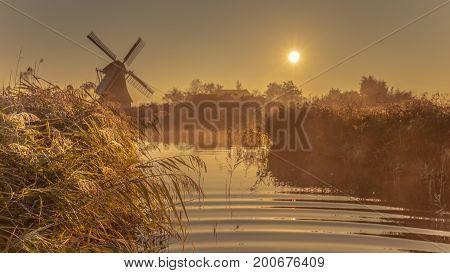 Dutch Windmill In Foggy Wetland