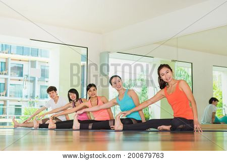 Yoga class in studio roomGroup of people doing seated side stretch right poses with calm relax emotionstreaching poseWellness and Healthy Lifestyle