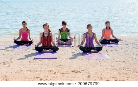 Yoga class at sea beach in sunny day Group of people doing lotus pose with clam relax emotionMeditation poseWellness and Healthy balance lifestyle.