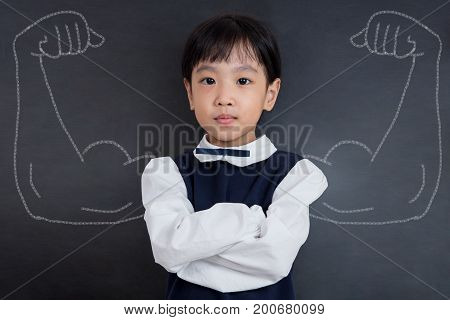 Asian Chinese Girl Standing Against Blackboard With Sketched Strong Arms