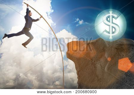 Businessman pole vaulting towards his money goal