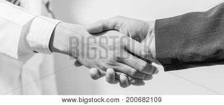 doctor and her lawyer shaking hands black and white.