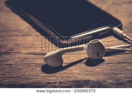 earphone and phone media portable on dark tone. earphone and smartphone on wood table. earphone and phone depth of field. White earphone and black smartphone. selective focus of earphone. earphone vintage. earphone music. earphone song. earphone sound.