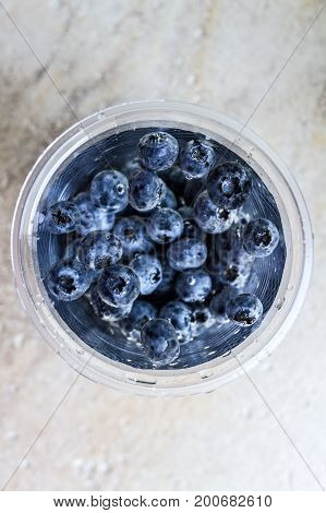 Ripe juicy blueberries in a glass with water on a stone background.