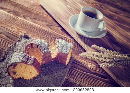 pie on bedding with the cup of coffee on a background a wooden table
