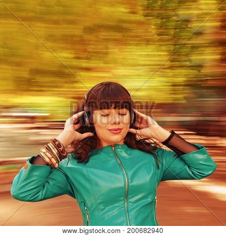 Happy woman having fun with music headphones. background with natural motion blur. Toned image with a square ratio