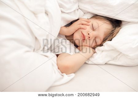 Portrait of cute little boy sleeping in white bed