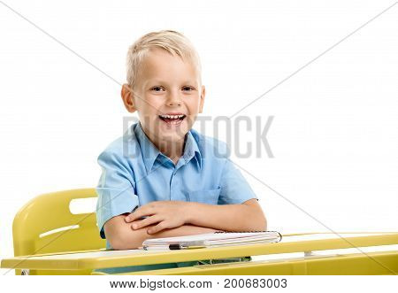 Portrait of laughing boy sitting at the desk with folded hands