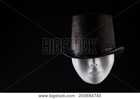 White maske hiding eyes under black top hat isolated on black background with copy space. Hidden personality concept