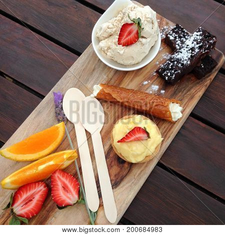 Dessert platter on wooden board with brownies tart orange fruit strawberries brandy snaps and disposable environmentally friendly spoons