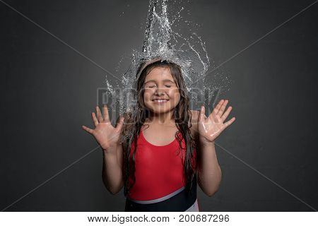 Happy teenaged girl in swimsuit catching water stream and splashes falling on her from top