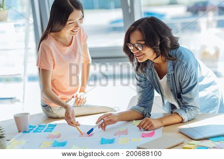 Creative project. Joyful happy smart women leaning over the table and discussing their project while studying together