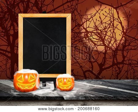 Blackboard with easel on grunge plank wooden and pumpkin with smoke on table top at spooky dead tree and full moonHalloween invitation cardTemplate mock up for display or montage of product.