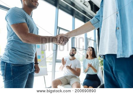 Start of cooperation. Close up of a friendly handshake between positive nice young men while starting their cooperation