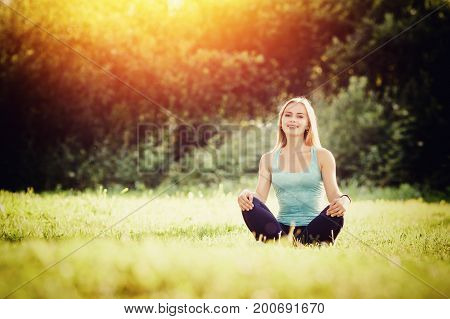 Young girl is engaged in yoga in the park in a lotus position, a glare of light. Concept meditation, a healthy body, outdoor activities, people and nature.