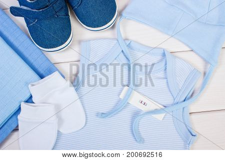 Test With Positive Result Of Pregnant And Clothing For Newborn, Expecting For Baby Concept