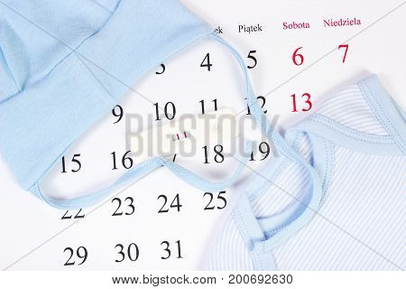 Pregnancy Test With Result Of Pregnant And Clothing For Newborn On Calendar, Expecting For Baby