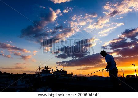 Silhouette of boy until is fishing on the dock at sunset.