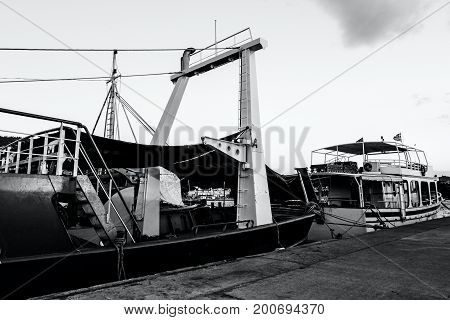 Fishing boat with metal construction are docked at pier harbor.