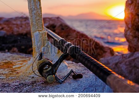 Fishing pole on a concrete with metal construction at purple sunset.