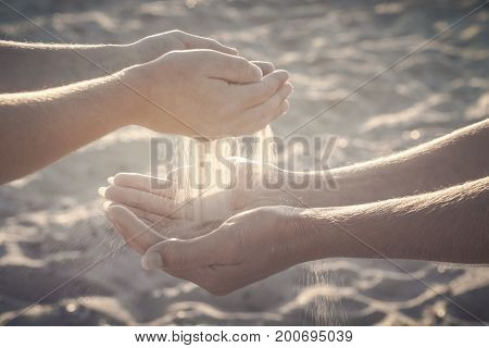 Child throws sand to the mothers arms. Active parents and people outdoor activity on summer vacations with children. Instagram stylization.