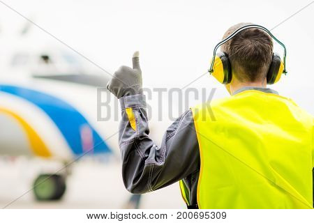 male airport worker thumb up success maintenance