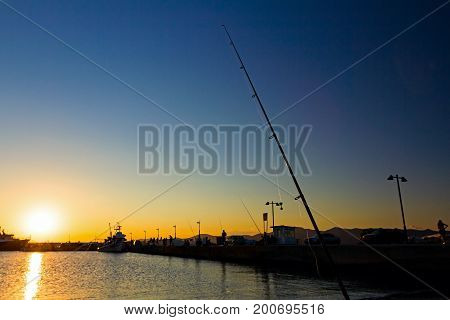 Silhouette of fishing pole on a beach dock at sunset is in background.