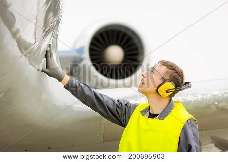 male airport worker servive ground preparation inspecting