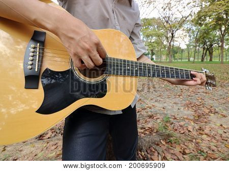 Wide angle shot of young man is leaning to play acoustic guitar at the park.