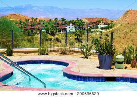 Jacuzzi taken poolside overlooking desert terrain and a contemporary residential neighborhood in Palm Springs, CA
