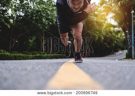 Runner running straight to camera on the road, with speed motion on border, selective focus on shoes