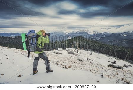 Photographer with a camera taking photos of beautiful winter mountain valley with dramatic clouds in a sky. Instagram stylization.