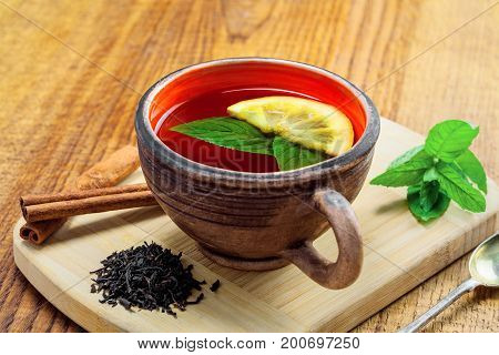 Cup of hot healthy herbal tea made of black Ceylon tea fresh mint leaves and lemon slice on a wooden table.