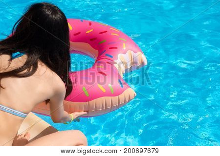 Girl with Inflatable swim ring in shape of donut ready to swim in the pool. Unrecognisable young woman wearing swimsuit having fun on pool party. Summer holiday and vacation theme